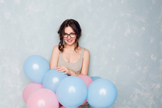 かわいいブルネットの少女がスタジオに立って、広く笑みを浮かべて、青とピンクの風船を保持しています。