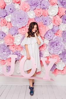 かわいいブルネットの少女が立ち、広く笑っている木の単語喜びを保持します。彼女は花で覆われたピンクの背景を持っています