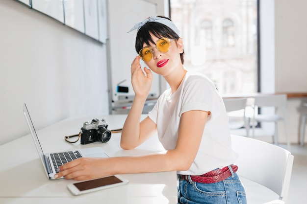 Cute brunette girl wears yellow glasses and leather belt working in office sitting with laptop and smartphone