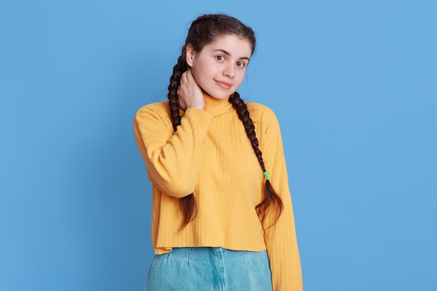 Cute brunette girl with braids wearing yellow sweater, looking at front with shy charming smile and holding her neck