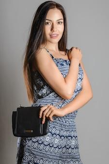 Милая брюнетка с длинными распущенными волосами держит черную сумочку