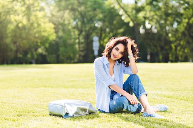 Милая брюнетка девушка с короткими волосами позирует на траве в парке. она носит белую футболку, рубашку и джинсы, туфли. она улыбается в камеру при солнечном свете.