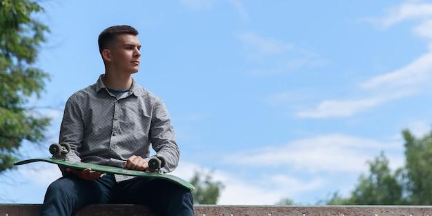 横を見て、暑い夏の日の青空の背景、コピースペースの公園でスケートボードのスライドに座ってスケートボードを保持しているかわいいブルネットの男