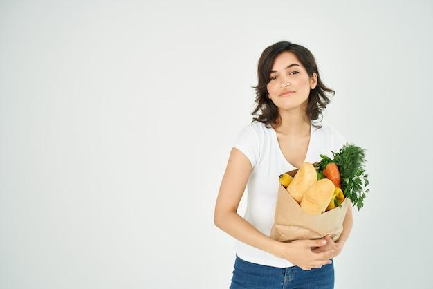 흰색 티셔츠를 입은 귀여운 갈색 머리가 식료품 가방을 들고 손 슈퍼마켓으로 몸짓