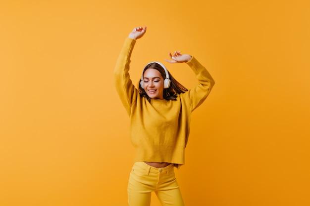 좋은 노래를 즐기는 노란색 바지에 귀여운 갈색 머리 아가씨. 오렌지 벽에 춤을 부드러운 스웨터에 평온한 여자.