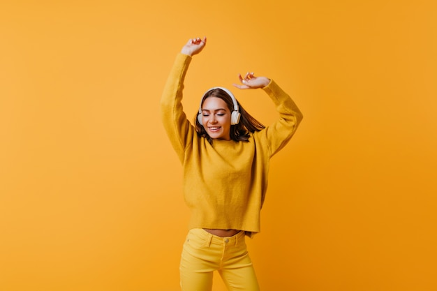 Cute brunette lady in yellow pants enjoying good song.  carefree woman in soft sweater dancing on orange wall.
