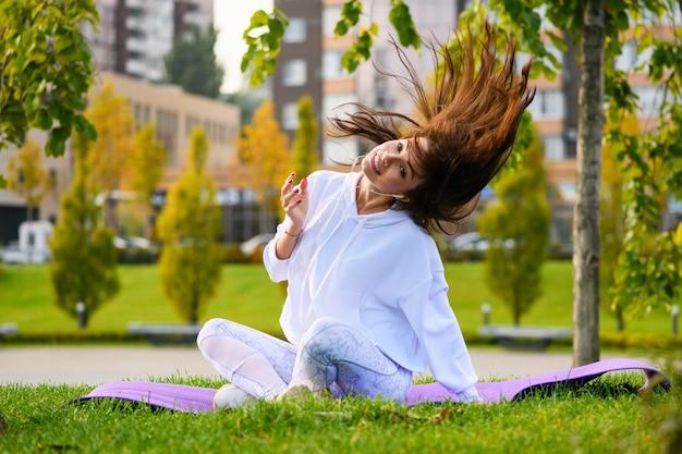Симпатичная брюнетка спортивная девушка в белой толстовке с капюшоном сидит на коврике на фоне городского парка с наушниками и танцами, двигает головой и волосами