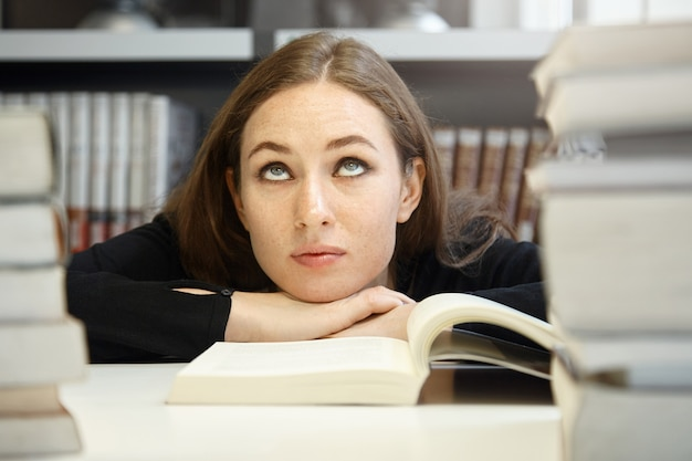 Симпатичная брюнетка студентка в черном пиджаке изучает и читает учебник или пособие в университетской библиотеке, но с трудом понимает материал, закатывает глаза, выглядит скучно и растерянно