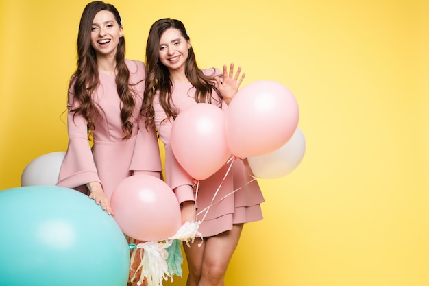 Cute brunette twins in pink dresses over yellow background