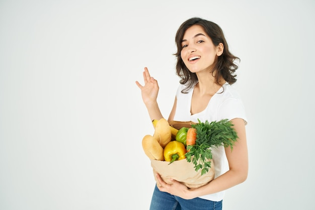 Cute brunette in a white tshirt a bag of groceries gesturing with a hand supermarket