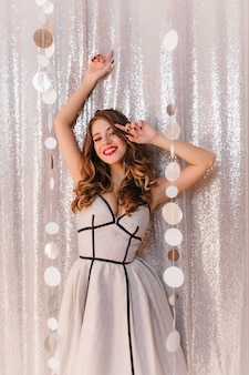 Cute brunette with hollywood curls in a silver cocktail dress at a festive party. girl smiling on glitter wall