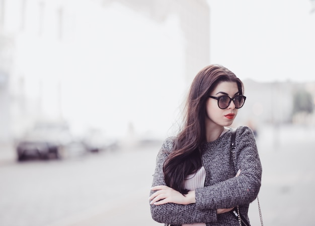 Cute brunette with red lips in sunglasses posing in city