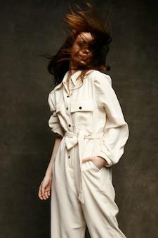 乱れた髪と暗い背景の上の白いジャンプスーツでかわいいブルネット