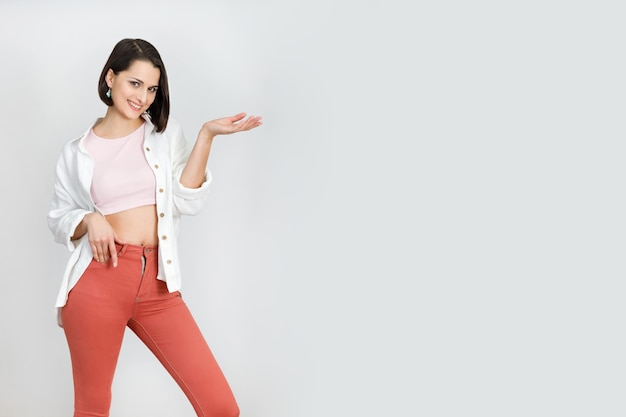 Cute brunette woman 30s in coral jeans pink tank top and white shirt on white background