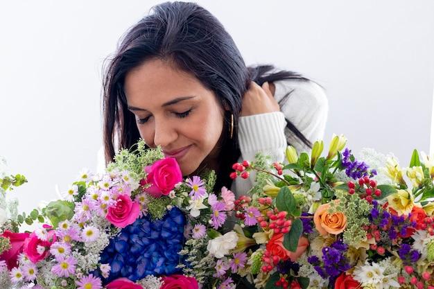 彼女の花束を楽しんでいるかわいいブルネットの女性
