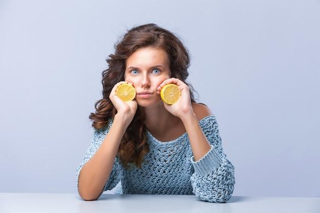 Милая брюнетка женщина держит в руках две половинки желтого лимона и цитрусовых с грустным лицом