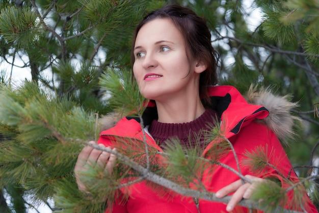 빨간 겨울 재킷을 입은 긴 머리를 가진 귀여운 브루네트 여성, 풀오버는 숲에 서서 바늘로 소나무 가지를 들고 있다