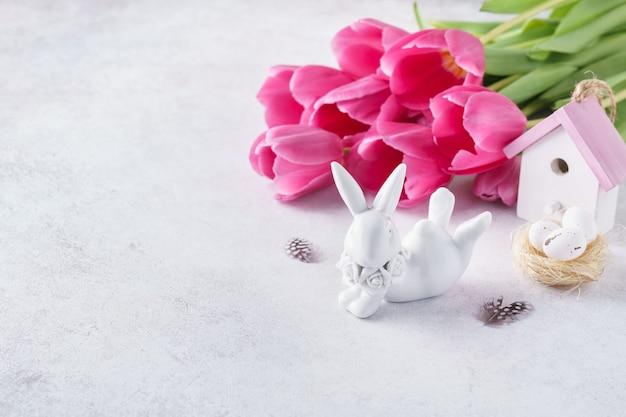 かわいいウサギ、ピンクのチューリップ、小さな家と巣。イースター、おめでとう。