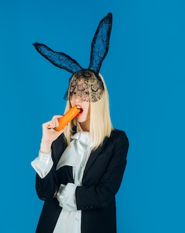 Cute bunny woman. happy young woman wearing bunny ears and having easter eggs. bunny rabbit eat carrot.