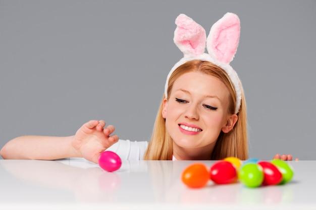 Милый кролик женщина с пасхальными яйцами