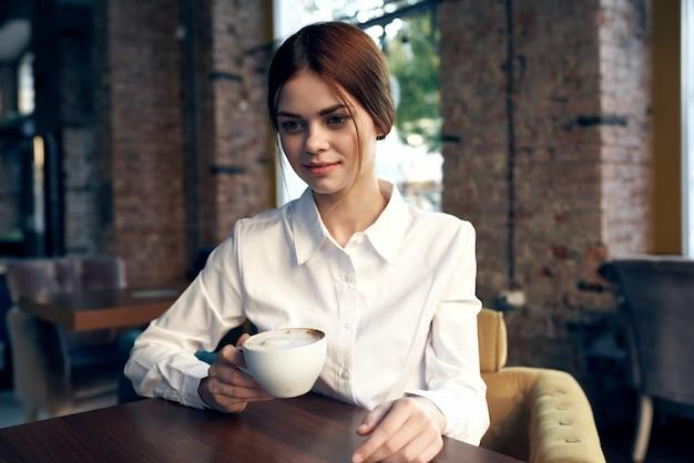 음료 라이프 스타일의 컵 테이블에 카페에 앉아 귀여운 비즈니스 우먼