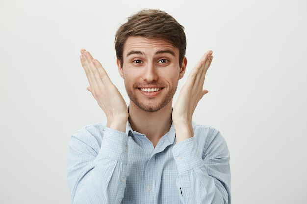 Cute businessman open eyes and smiling surprised