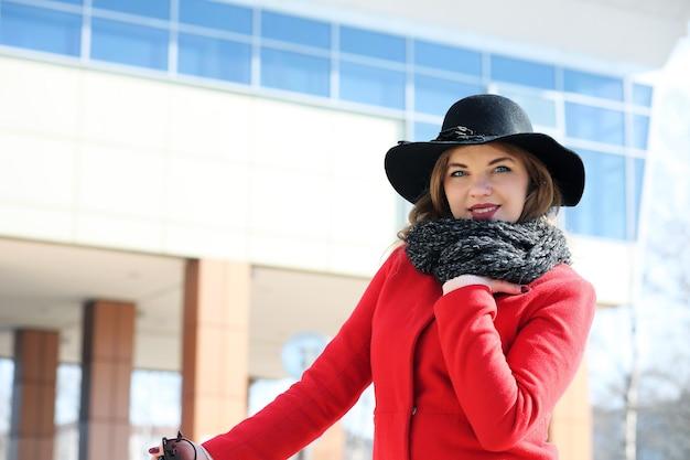 Милая бизнесвумен в красном пальто на фоне небоскребов