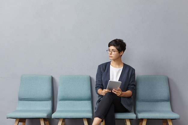 Cute businesswoman looks pensively aside, waits meeting with partners