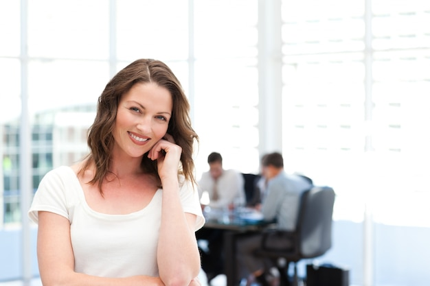 Cute businesswoman standing in front of her team while working