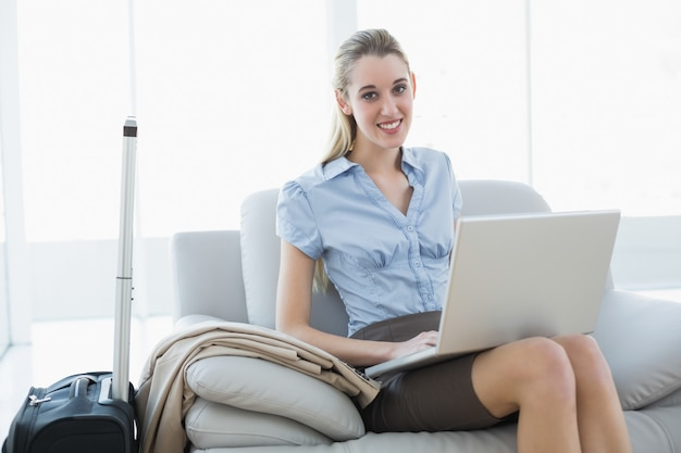Cute businesswoman using her notebook sitting on couch
