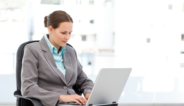 Cute businesswoman working on the laptop sitting at her desk