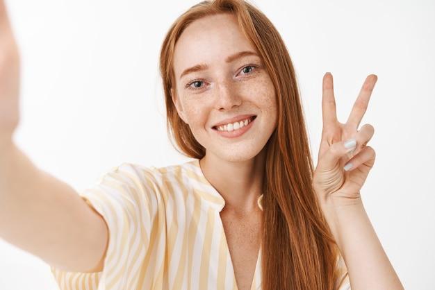Carina giovane femmina rossa spensierata e felice con le lentiggini in abito estivo giallo prendendo selfie