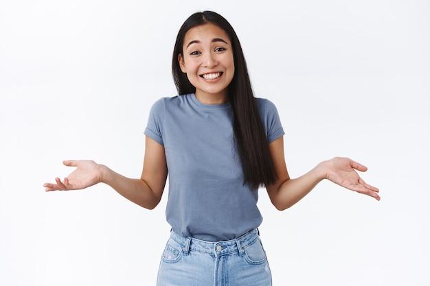 Carina spensierata, rilassata donna asiatica sorridente che alza le spalle, inclina la testa sciocca e allarga le mani lateralmente indesicisive, non importa, non ne ho idea e non mi preoccuperò di questo, in piedi muro bianco incurante
