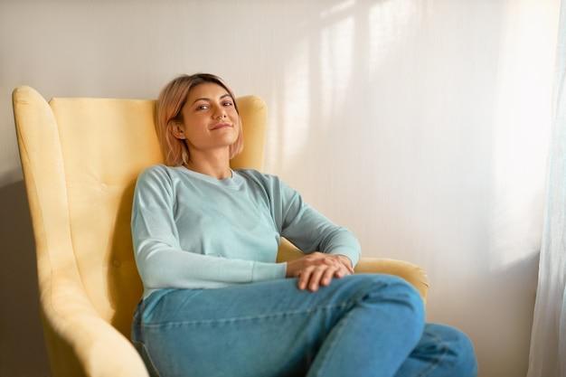 白いカーテンの上の黄色い肘掛け椅子に座ってカジュアルな服を着ているかわいいのんきな若い白人女性
