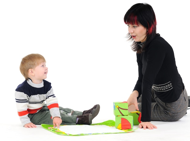 Cute caring young mother is talking with her little unidentified child on a white wall. concept of parent-child communication and child care. advertising space
