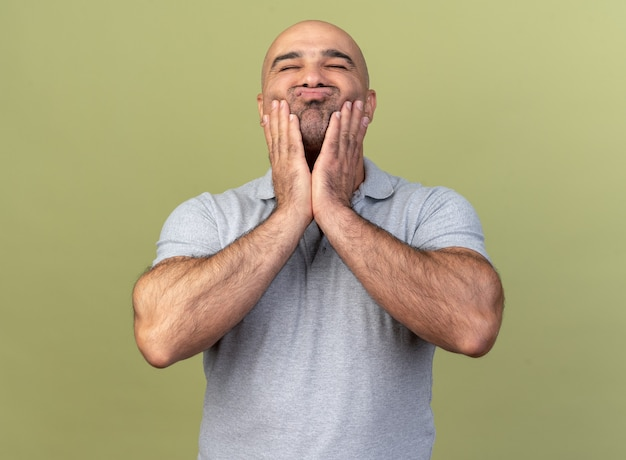 Cute casual middle-aged man keeping hands on cheeks pursing lips with closed eyes isolated on olive green wall