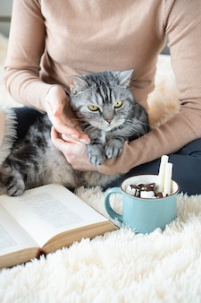 Cute cat in female hands. cup of tasty cocoa and book on the soft blanket. cozy home atmosphere. text in the book is not recognizable.
