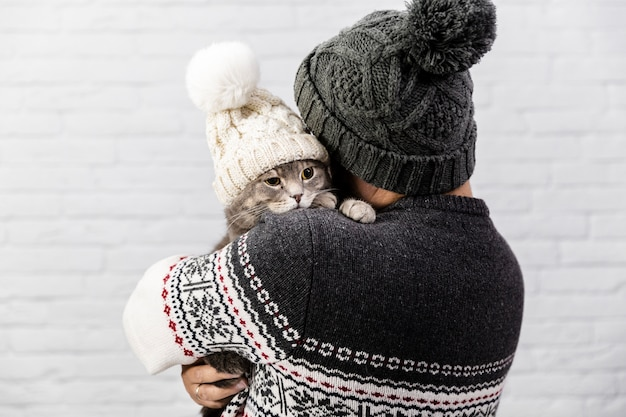 Cute cat with hat held by owner