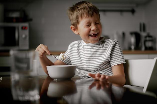 귀여운 백인 6살 소년이 아침 식사로 오트밀을 먹고 웃고 있다