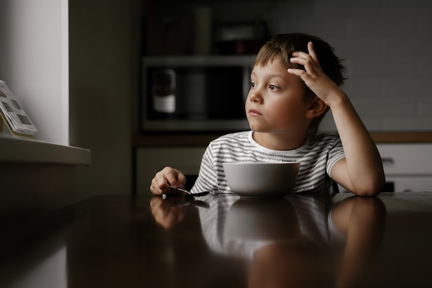 귀여운 백인 6살 소년이 아침에 오트밀을 먹고 창문을 바라보고 있다