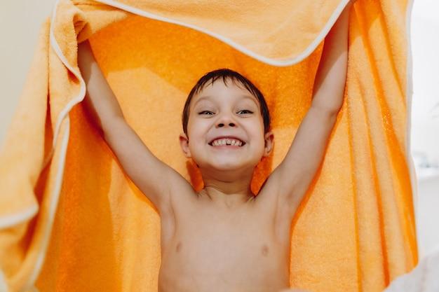 샤워 후 주황색 수건을 들고 앞니를 잃은 귀여운 백인 6세 소년