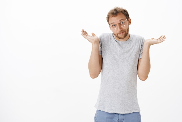Cute caucasian adult bearded man in glasses and casual grey t-shirt shrugging with hands up smiling with sorry look being unaware and clueless over white wall