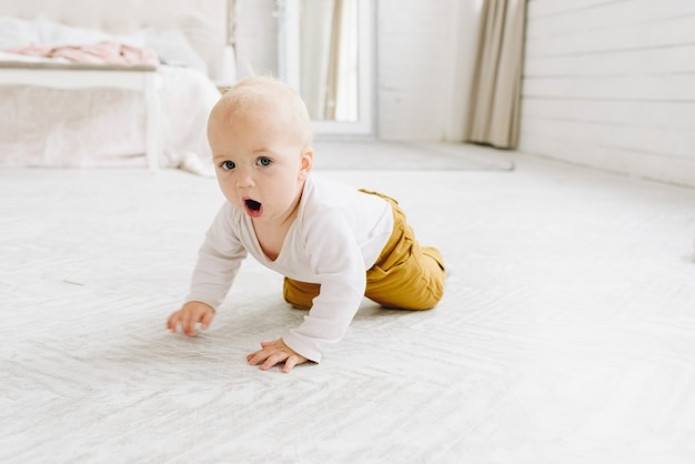 Cute caucasian baby crawling in a light bedroom