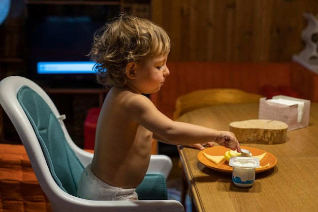 Милый кавказский ребенок ест за столом. малыш ест сам за взрослым столом