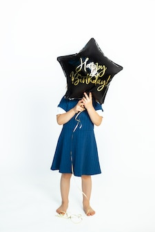 A cute caucasian baby girl covers her face with black gel balloon that says happy birthday. photo in studio against a white background