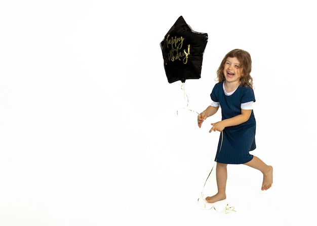 Cute caucasian baby girl running happily with black gel star balloon with inscription happy birthday. photo in studio against a white background