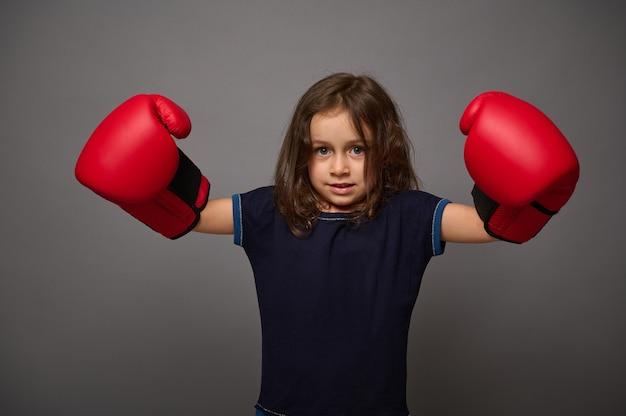 赤いボクシンググローブを身に着けているかわいい白人の女の赤ちゃんは、ボクシングデーの広告のコピースペースで灰色の壁の背景にポーズをとる