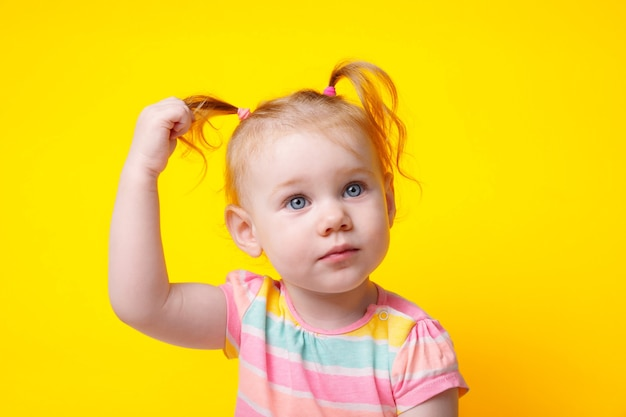 Cute caucasian baby girl with ponytails over yellow background