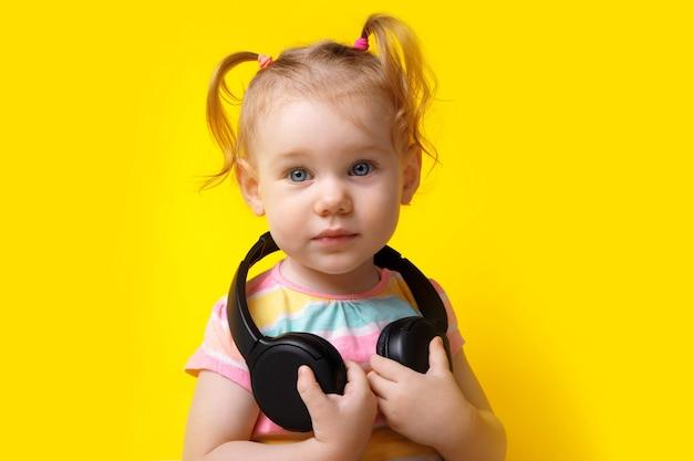 무선 헤드폰을 끼고 있는 귀여운 백인 아기, 노란색 배경에서 카메라를 바라보는 어린 소녀