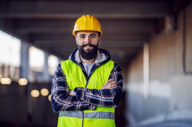 Cute caucasian bearded construction worker with safety helmet on head in vest standing with arms crossed at construction site